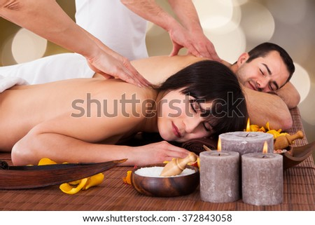 Relaxed young couple receiving back massage at beauty spa