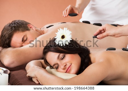 Relaxed young couple receiving hot stone therapy at beauty spa - stock photo