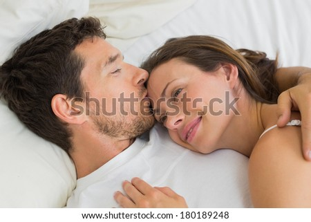 Relaxed young couple sleeping together in bed at home - stock photo