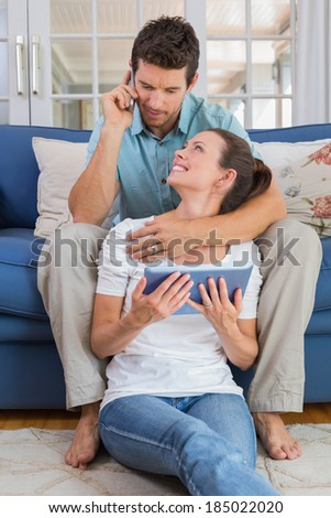 Relaxed young couple using digital tablet and cellphone in the living room at home - stock photo