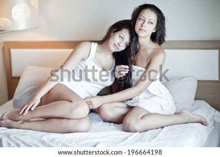 Relaxed young female friends with book gossiping in bed at home - stock photo