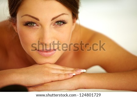 Relaxed young female getting a stone massage in a spa