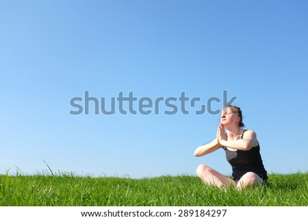 Relaxed young girl sitting outdoor in green meadow