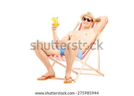 Relaxed young guy drinking a refreshing cocktail seated in a sun lounger chair isolated on white background - stock photo