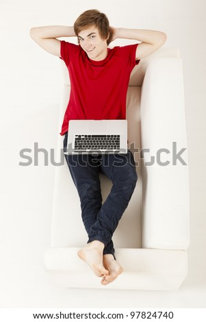 Relaxed young man at home lying on the couch with a laptop - stock photo