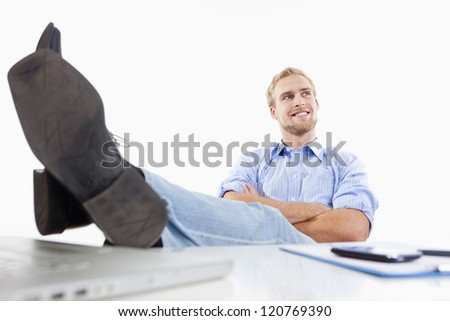 relaxed young man at office with his feet on the desk