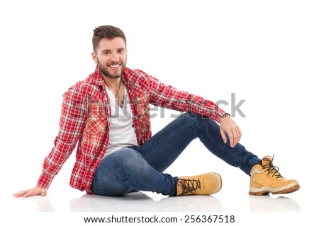 Relaxed young man in lumberjack shirt sitting on a floor and and looking at camera. Full length studio shot isolated on white. - stock photo