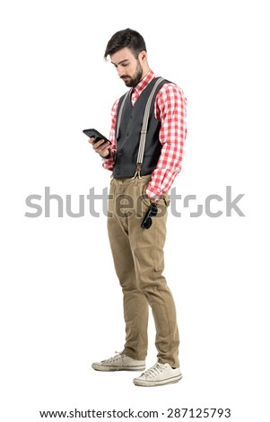 Relaxed young man in retro clothes typing message on smartphone.  Full body length portrait isolated over white studio background.