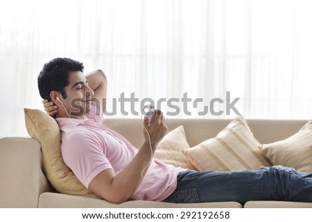 Relaxed young man listening to music at home - stock photo