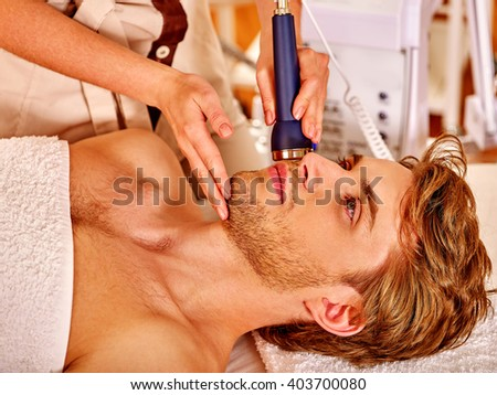 Relaxed young man luxuriating on electroporation  facial therapy at beauty salon.  - stock photo
