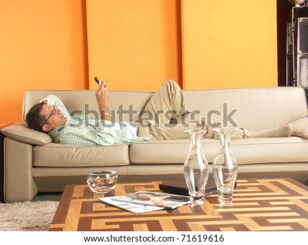 Relaxed young man lying down on sofa with a mobil phone. - stock photo