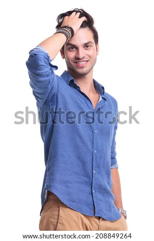 relaxed young man passing hand through his hair to fix his hair style - stock photo