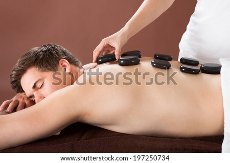 Relaxed young man receiving hot stone therapy in spa - stock photo
