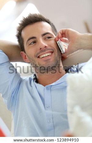 Relaxed young man talking on the phone in sofa - stock photo