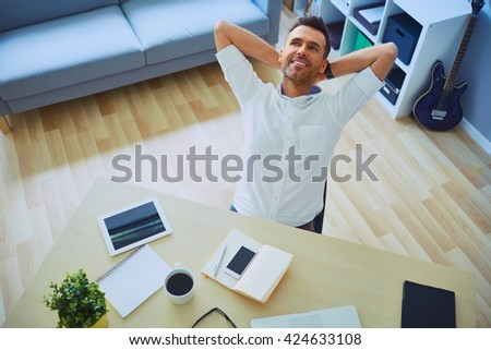 Relaxed young man with hands behind head working form home office - stock photo