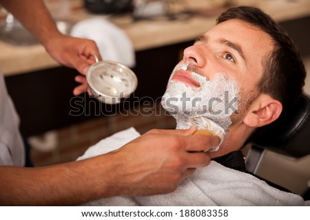 Relaxed young man with shaving cream on his face and ready to get his beard shaved - stock photo