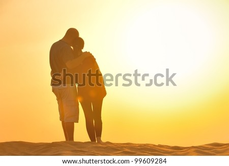 relaxed young pasionate couple enjoying the sunset  beauty on their honeymoon, on a desert with orange background - stock photo