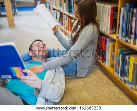 Relaxed young romantic couple with books at the library aisle - stock photo