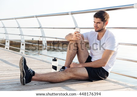 Relaxed young sportsman resting and using mobile phone sitting on wooden terrace - stock photo
