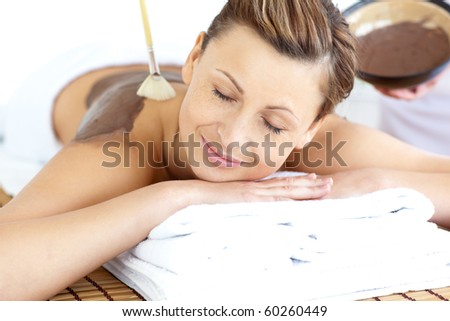 Relaxed young woman enjoying a beauty treatment with mud in a health spa - stock photo