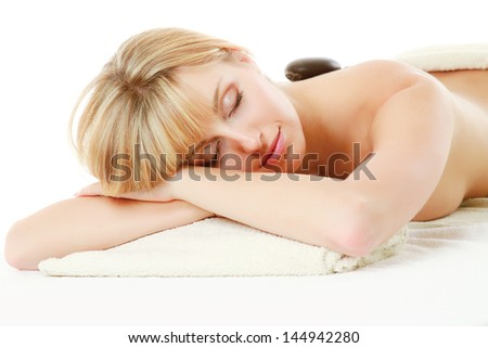 Relaxed young woman getting hot stone message at spa salon isolated on white - stock photo