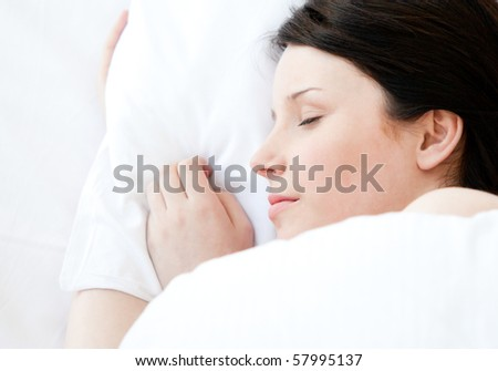 Relaxed young woman lying in a bed sleeping at home - stock photo