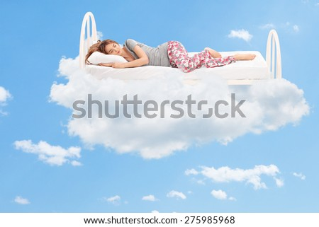 Relaxed young woman sleeping on a comfortable bed in the clouds - stock photo