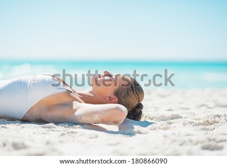Relaxed young woman tanning on beach - stock photo