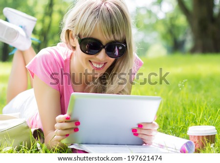 Relaxed young woman using tablet computer outdoors - stock photo