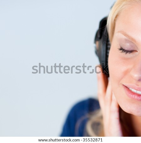 Relaxed young woman with closed eyes listening music with headphoness and looking at the camera