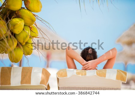 Relaxed young women lying on beach lounger near coconut tree - stock photo