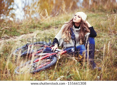 Relaxes woman cyclist with bike sits among yellow grass