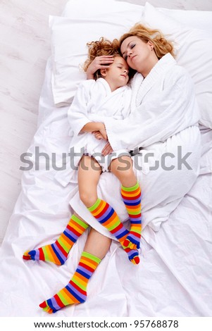 Relaxing after bath - woman and little girl in bathrobes - stock photo