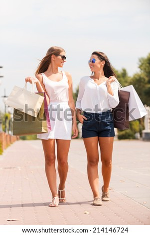 Relaxing after day shopping. Full length of two beautiful young women with shopping bags walking by the street together and smiling - stock photo