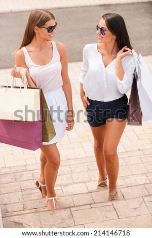 Relaxing after day shopping. Top view of two beautiful young women with shopping bags walking together and talking - stock photo