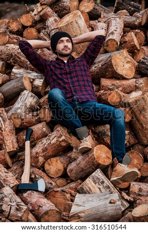 Relaxing after hard working day. Full length of confident young forester holding head in hands and looking up while leaning at the logs - stock photo