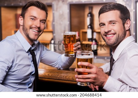 Relaxing after hard working day. Two happy young men in shirt and tie holding glasses with beer and smiling while sitting at the bar counter  - stock photo