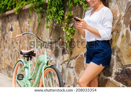 Relaxing after long ride. Beautiful young woman holding mobile phone and smiling while standing near her vintage bicycle  - stock photo