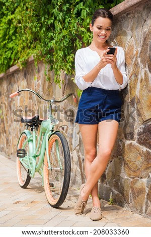 Relaxing after long ride. Full length of beautiful young woman holding mobile phone and smiling while standing near her vintage bicycle  - stock photo