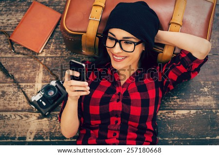 Relaxing after long trip. Top view of beautiful young woman in headwear lying on the floor holding mobile phone and smiling - stock photo