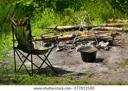 Relaxing and preparing food on campfire in camping, summer scene outdoors - stock photo