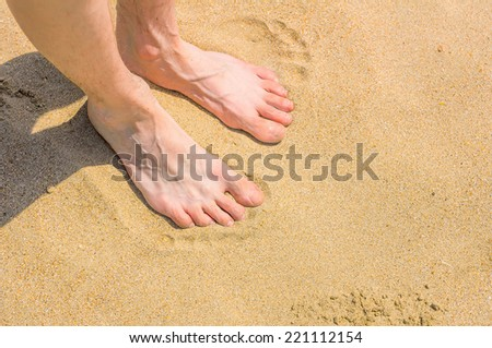 Relaxing at a beach, with your feet in the warm sand.