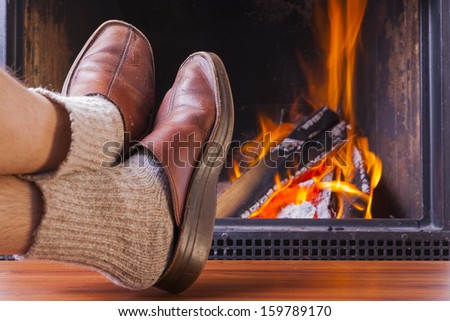 relaxing at homely warm fireplace - stock photo