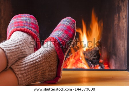 relaxing at the fireplace on winter evening - stock photo