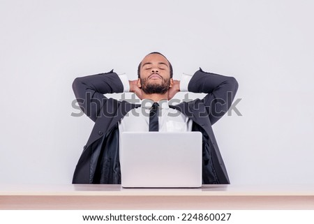 Relaxing at work. Smiling African businessman sitting at a desk on a laptop while a businessman sitting at a table and  holding his hands behind his head on isolated gray background