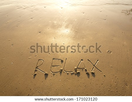 Relaxing Beach - Relax written in the sand. - stock photo