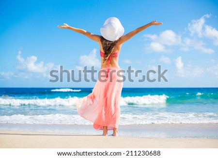 Relaxing beach vacation. Happy woman enjoying sunny day at the beach. Open arms, freedom, happiness and bliss.  - stock photo