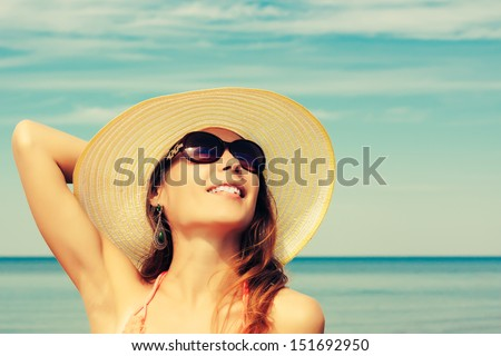 Relaxing beach woman enjoying the summer sun happy in a wide sun hat and sunglasses at the beach - stock photo