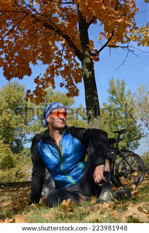 Relaxing bicyclist in autumn park - stock photo