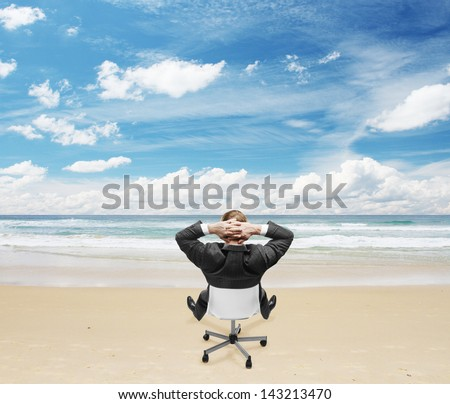 relaxing businessman sitting on beach - stock photo